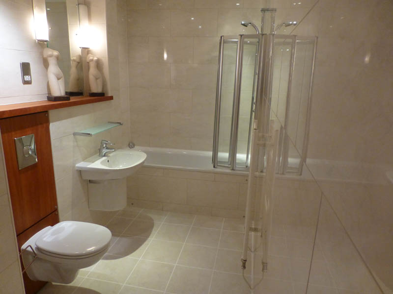 Bathroom with bathtub and shower over.