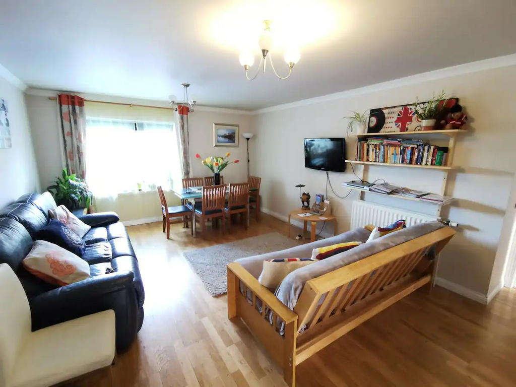 Large living room with 2 sofas and a dining table, open view towards Meadowbank church