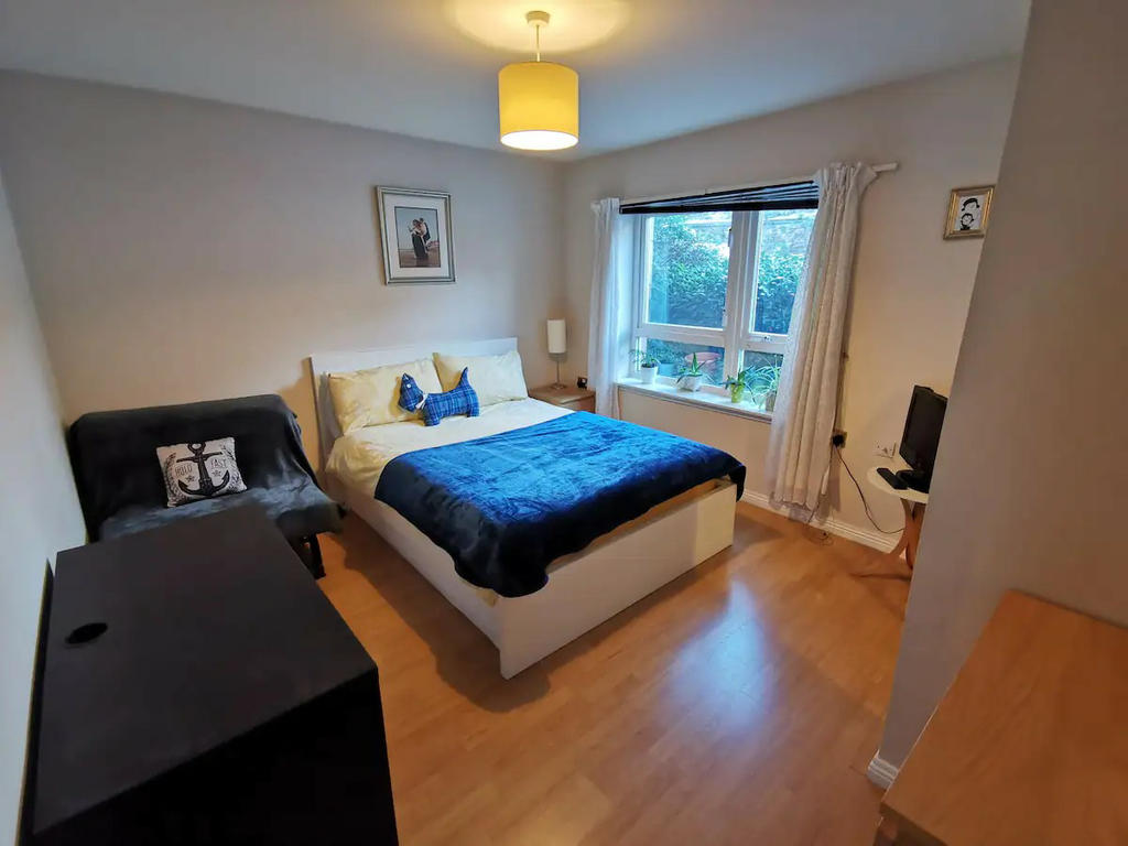 Double bedroom 1 with mirrored wardrobe, bedside cabinet, chest of drawers, TV and a small sofa