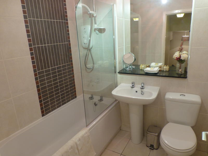 The bathroom has a bathtub with shower over