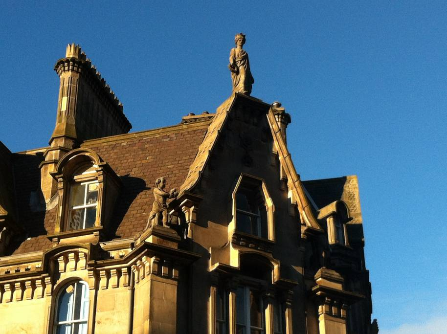 A statue of Queen Victoria perches high on the roof of the building