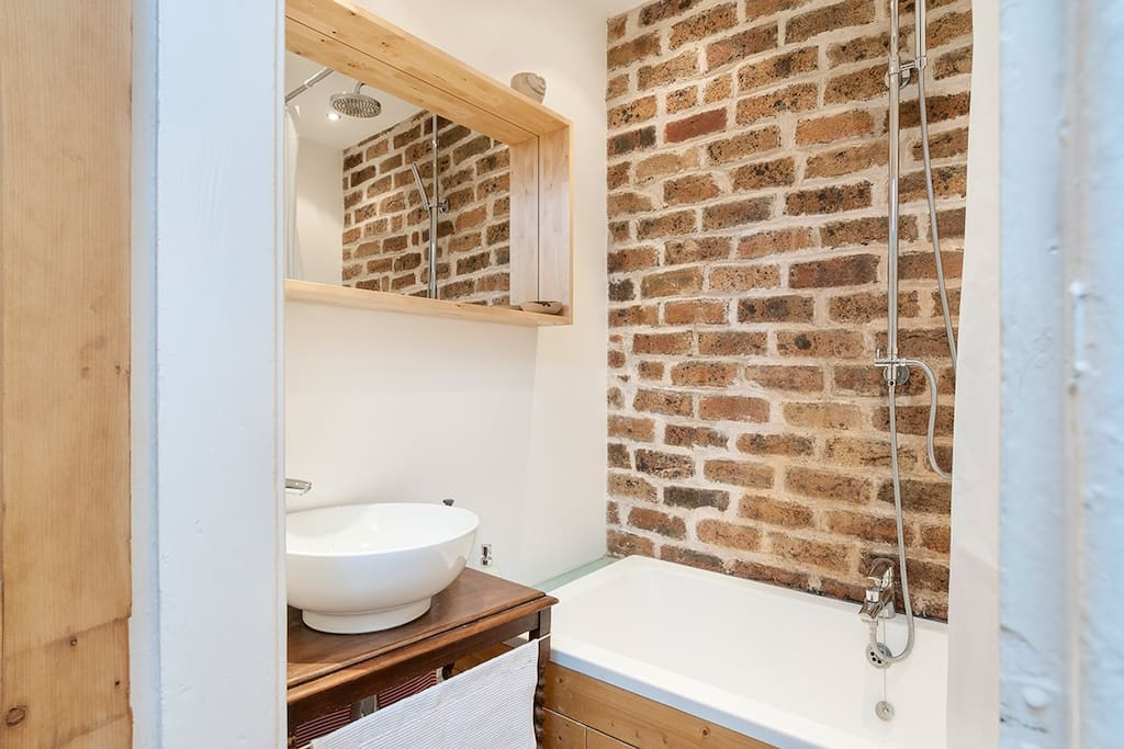 Contemporary bathroom with rain shower over bath, feature stone wall and underfloor heating
