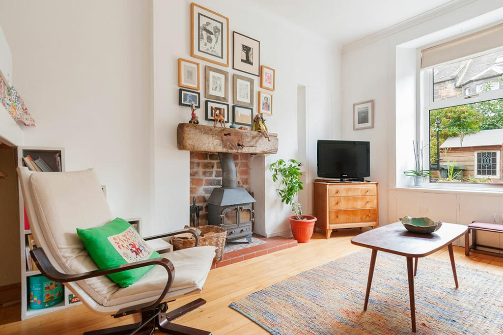 Art filled living room with wood burning stove and view into private garden